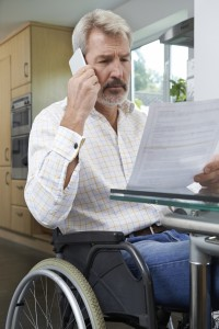 Frustrated Man In Wheelchair Making Phone Call Whilst Reading Le