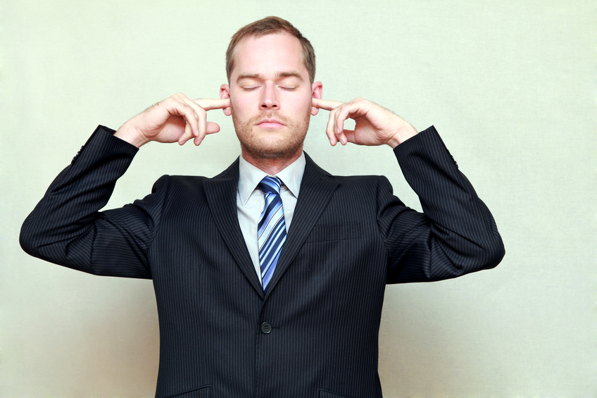 Portrait of young handsome businessman with closed eyes and fingers in ears, not listening, isolated on gray