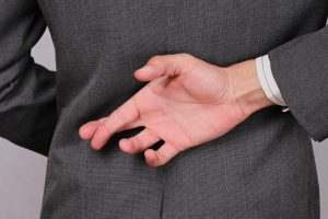 Liar businessman with crossed fingers at back . Ethics concept. Unfair business practices