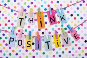 Colorful cheerful think positive message on colorful dots background