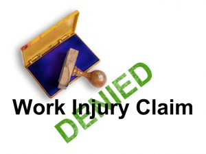 "Top view of a rubber stamp with a giant word ""Work injury claim - denied "" isolated on white background"